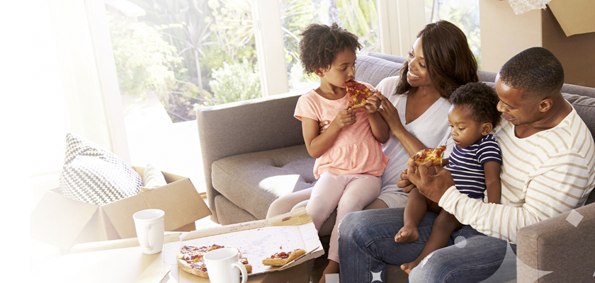 Family eating pizza on the couch