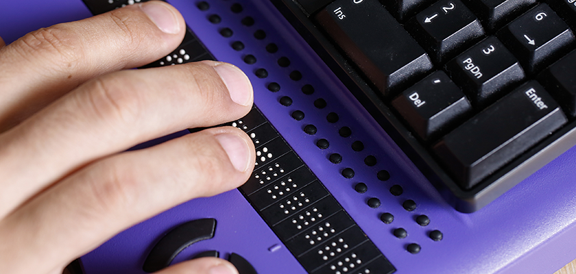 Person typing on braille keyboard