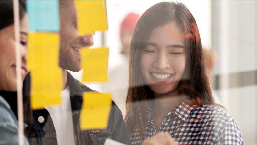 Woman and team smile and brainstorm with sticky notes