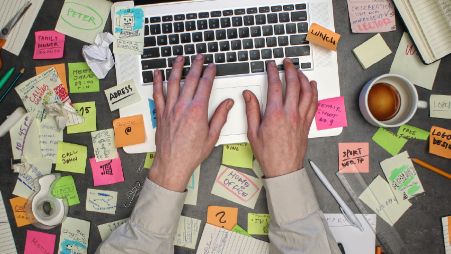 Man working on laptop with notes all around his office desk