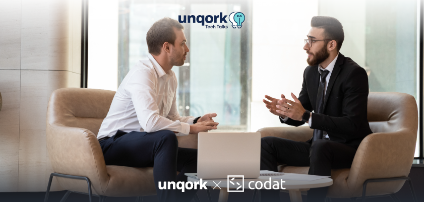Two businessmen talking with Unqork and Codat logos superimposed over image