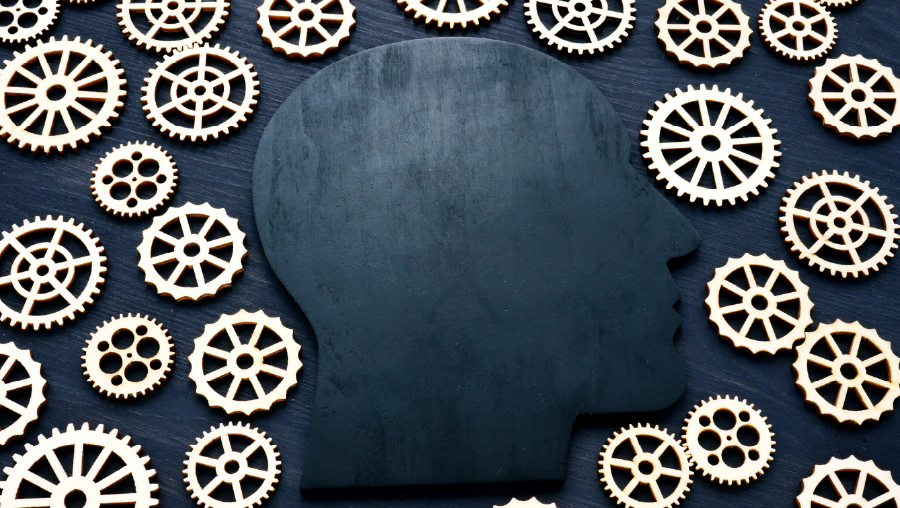 Head silhouette surrounded by gears