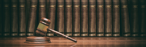 A gavel with legal books in the background.