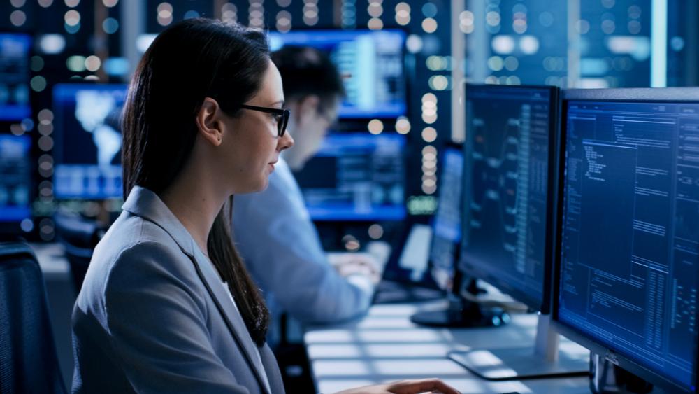 Female security engineer looking over monitors.