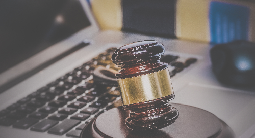 A gavel on a desk in front of a computer.