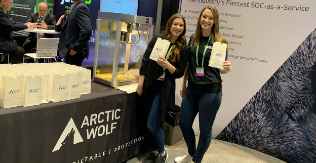 Two Arctic Wolf pack members holding up popcorn bags at our RSA 2020 booth.