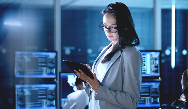 Woman holding a tablet while at work in a cybersecurity center.