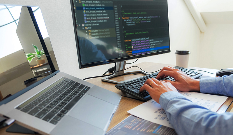 Security engineer in front of a laptop with two screens.