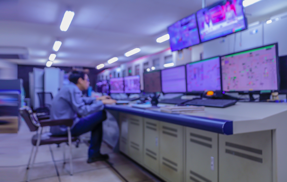 Blurred out image of a cybersecurity professional working in front of a series of monitors.