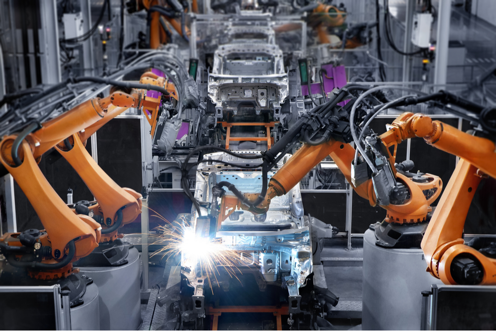 Inside of an automotive plant, there is an assembly line of unfinished cars being built.