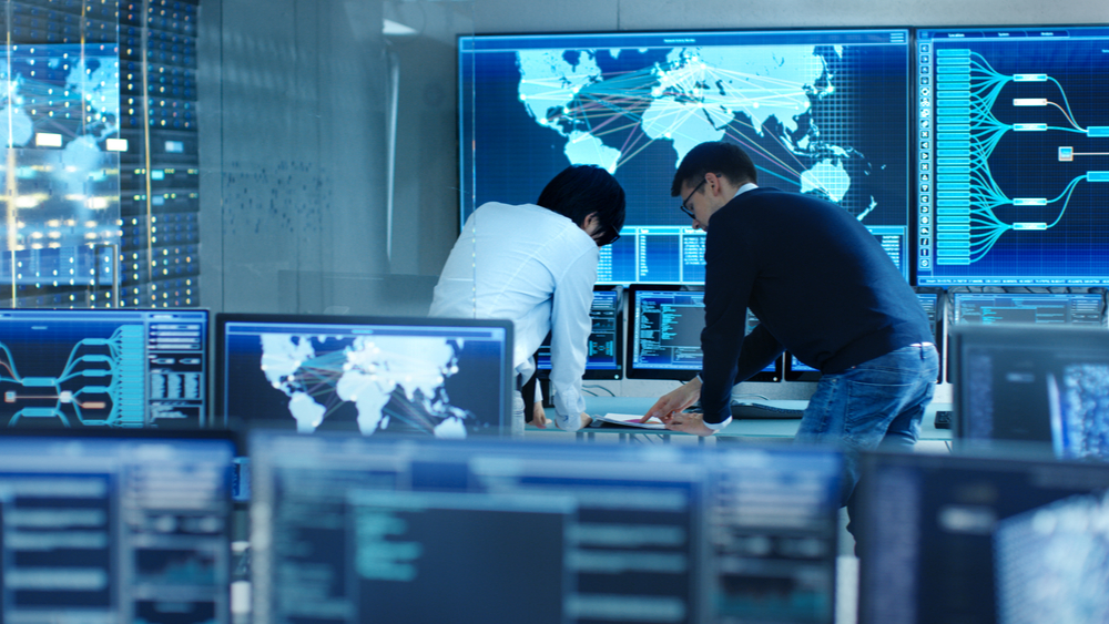 See a couple of cybersecurity engineers looking over a computer inside of a data center.