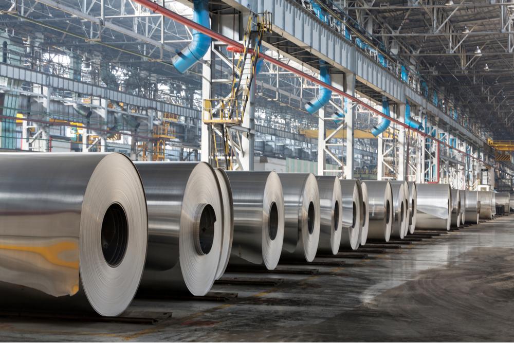 Large rolls of aluminum inside of a manufacturing building.