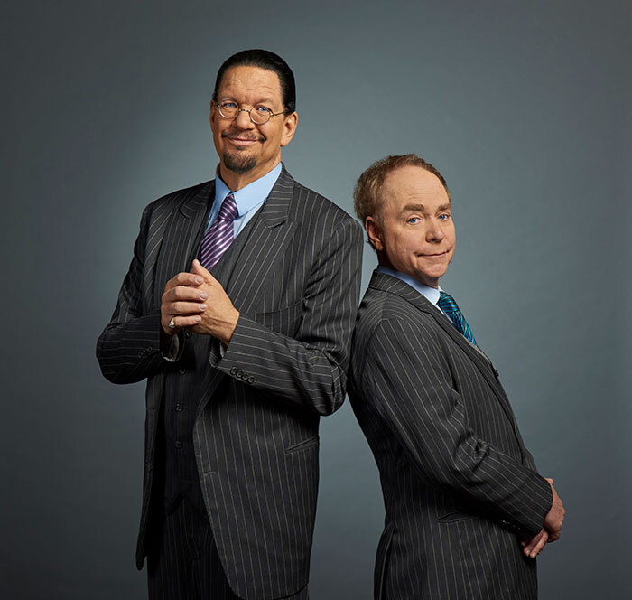A photo of Penn and Teller standing back to back.
