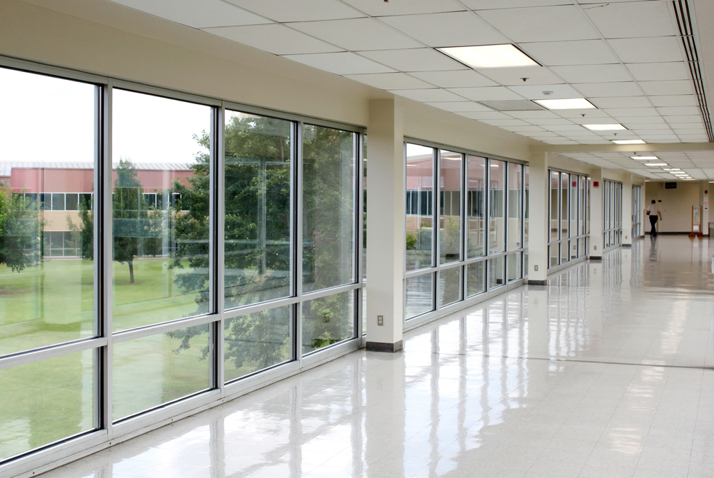 Inside of a school. An empty hallway with a view of trees outside.