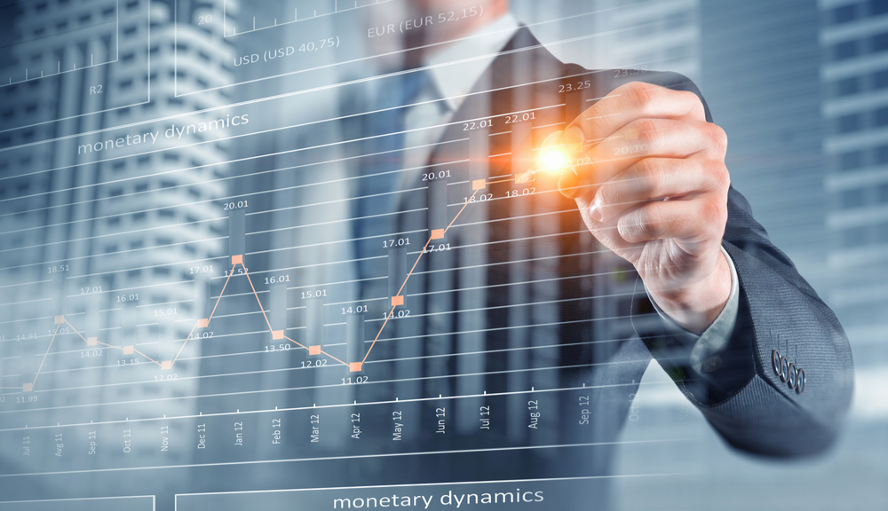 """""""monetary dynamics"""" is written on the screen with a man looking over a rising bar chart"""