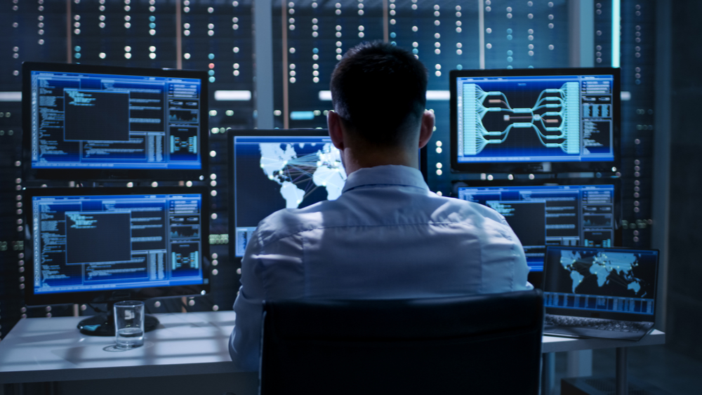 See a cybersecurity personnel in front of a his laptop and a series of monitors.