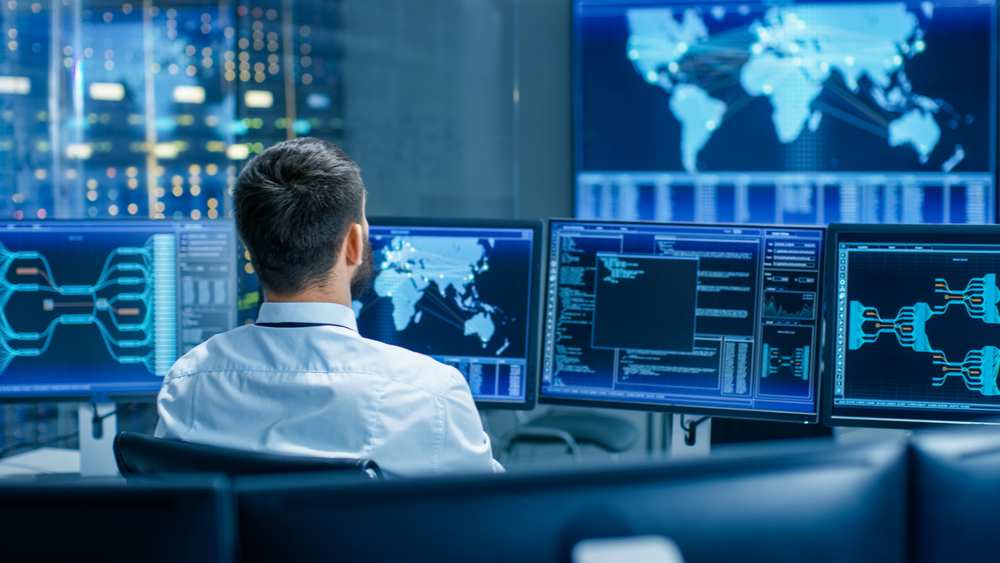 A security analyst looking over a series of monitor. The average analyst is over $90,000 a year.