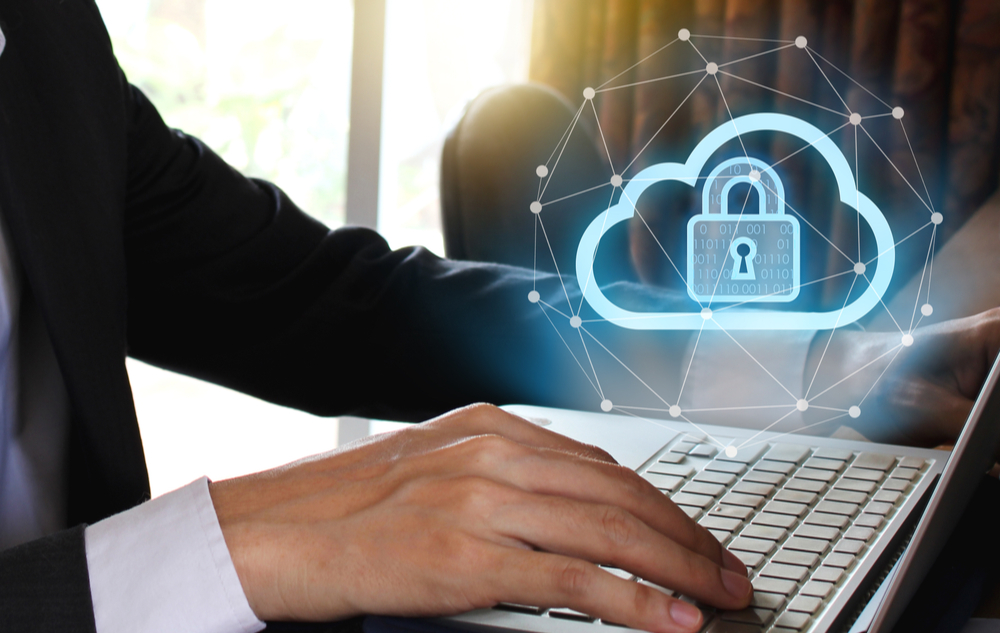 A man on his laptop with a cloud security symbol and a lock above the screen.