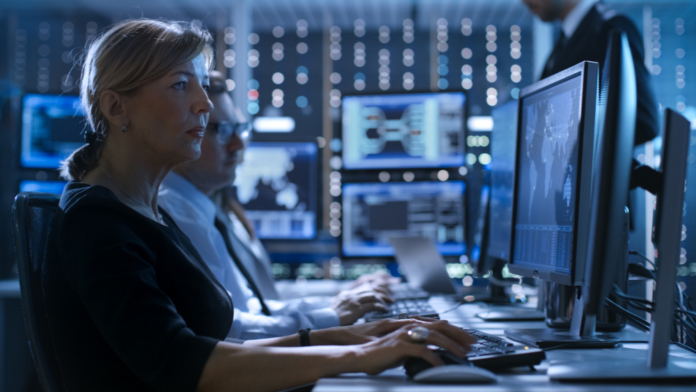with the growing cybersecurity skills gap, there's less trained professionals for organizations to hire. Inside of a security operations center, a man and woman are working