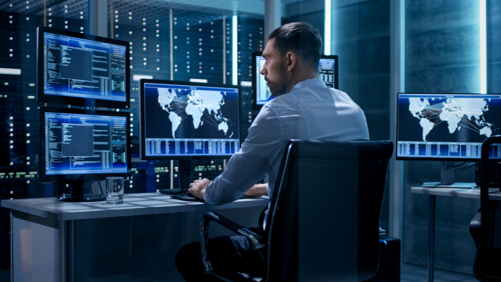 Security operations is setting the standard for cybersecurity. We see a security operations expert in front of multiple computer screens.