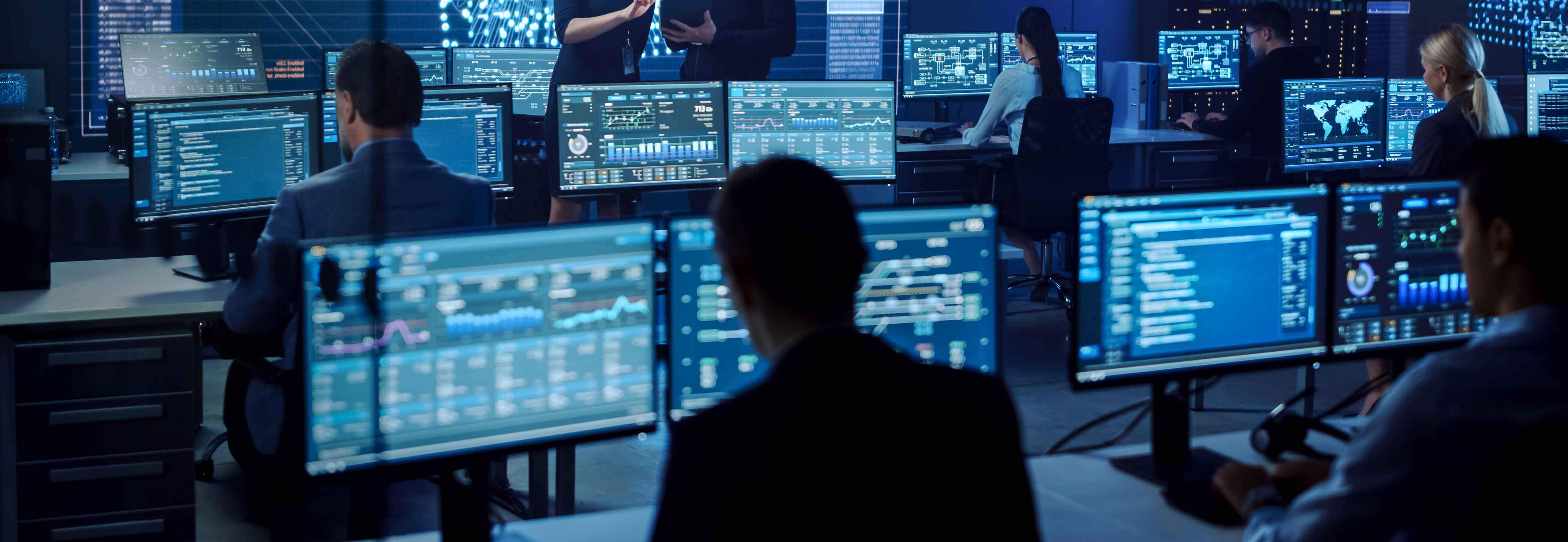 Security analysts in a data center. An abundance of screens and complexity.
