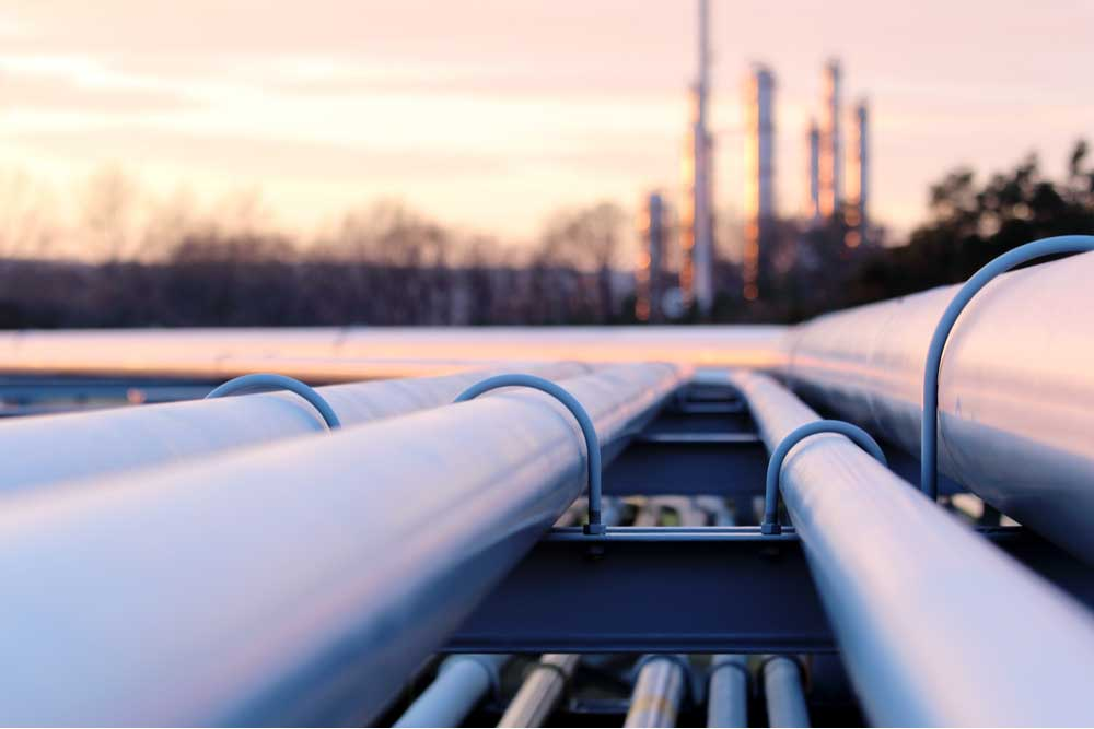 Close up of a pipeline with a factory in the background.