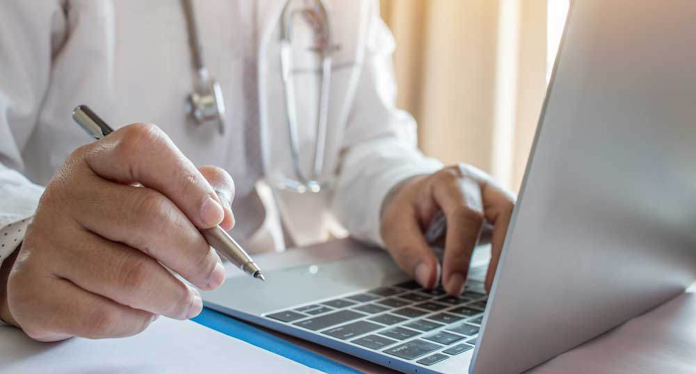 Doctor holding a pen in front of a laptop