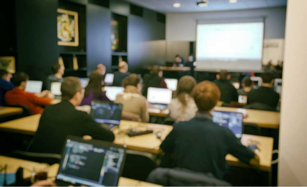 In a classroom, a group of students are in front of computers at their individual desks.