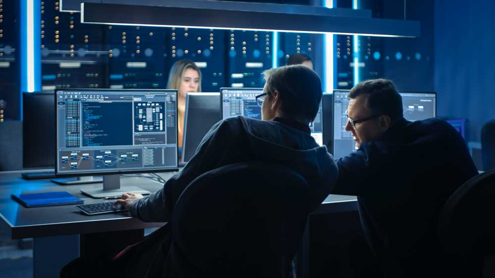 Four cybersecurity professionals in front of their monitors, looking at data.
