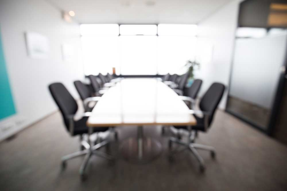 An empty boardroom with a blurred out background.