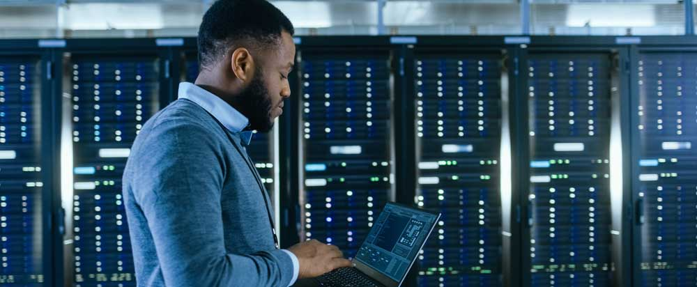 Male cybersecurity engineer looking at his laptop.