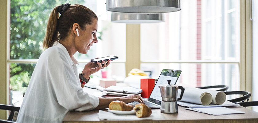 Woman in kitchen on phone and laptop