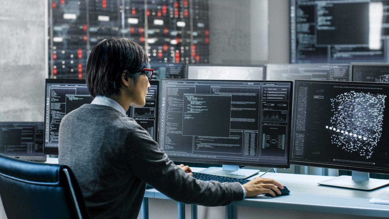 Man looking at multiple monitors