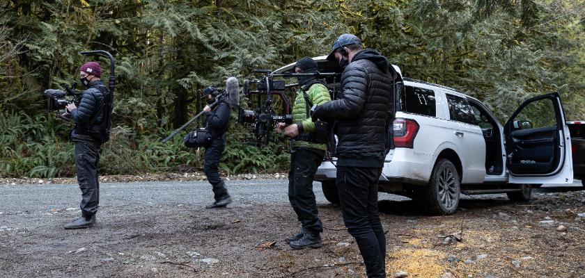 four cinematographers holding film equipment