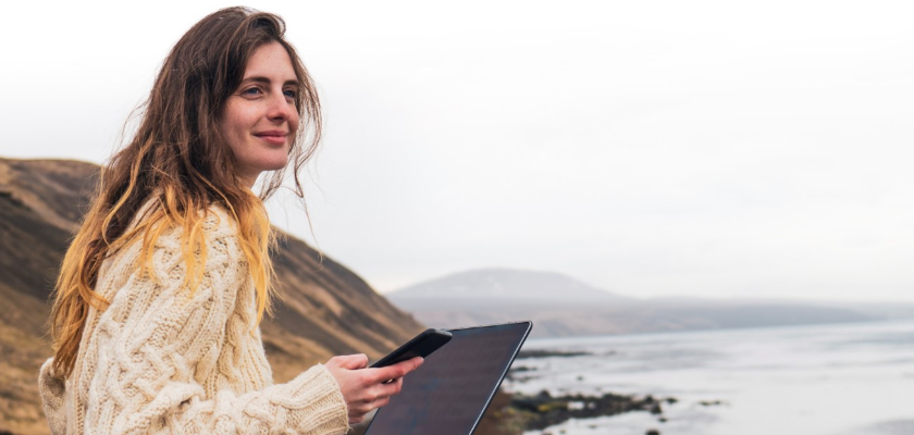 Young female working remotely from laptop by coastal waters