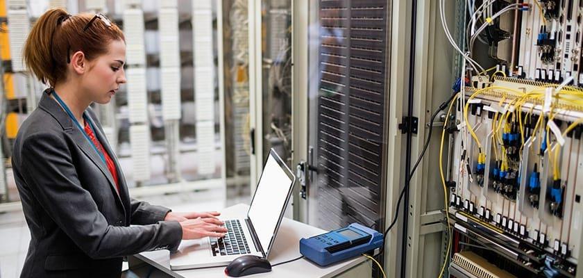 Femme sur ordinateur portable devant les serveurs