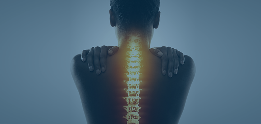 Woman holding her back, with exposed lit up spine