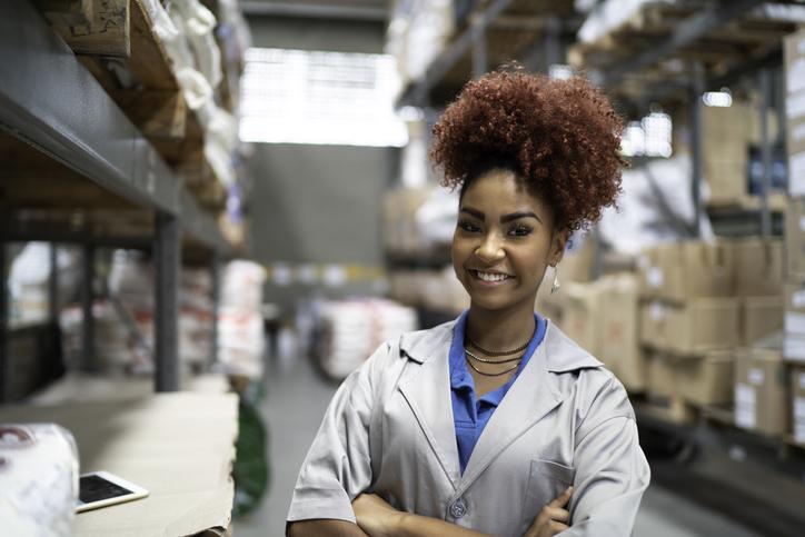 A smiling gen z aged worker in a warehouse