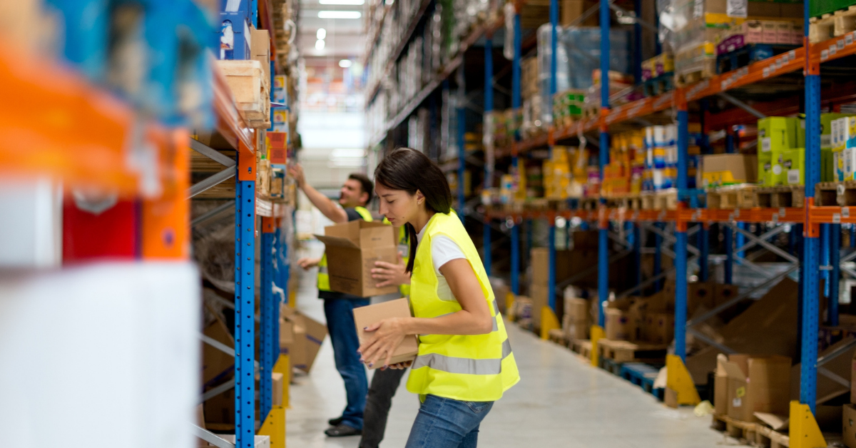 A warehouse worker stacking a box in a distribution center