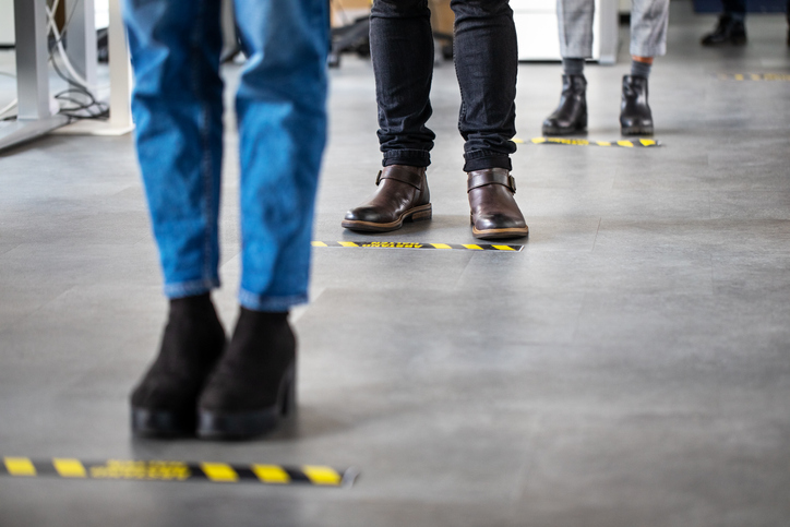 People standing 6 feet a part at work