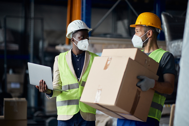 Two workers in a warehouse who have learned the art of staffing retention