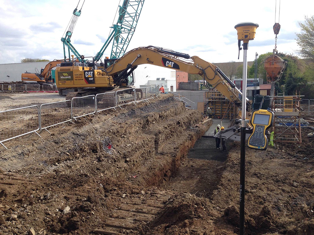 maverick cat excavator with trimble machine control and worker with trimble construction surveying equipment