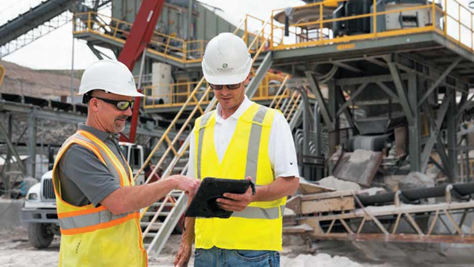 quarry managers looking at tablet