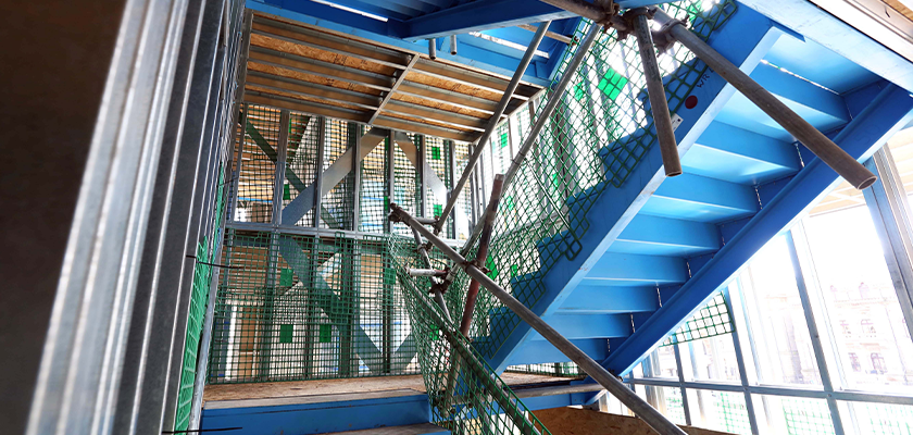 Stairwell under construction, steel stair with temporary handrail made of scaffolding and mesh surrounded by light steel framing