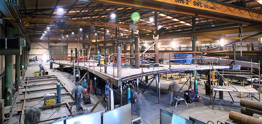 People working on a canopy section in the fabrication shop