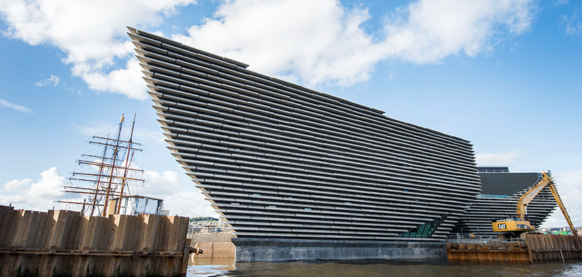 View looking up from ground level at V&A Dundee, triangular shape façade of precast rough stone panels