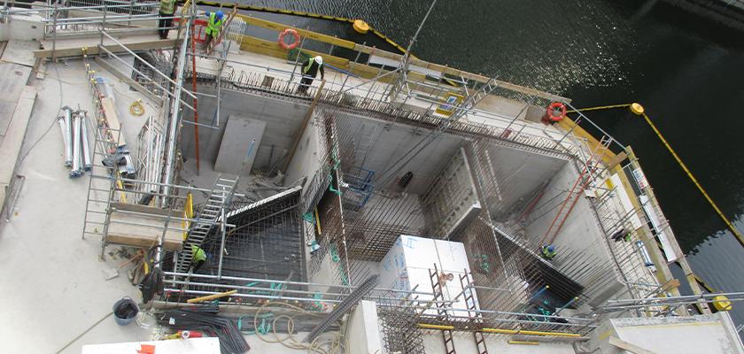 Workmen on temporary walkway looking down into section of Water Street Bridge