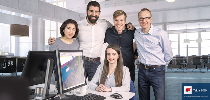 People stood together smiling, monitor in foreground displays Tekla Structures 2019 model