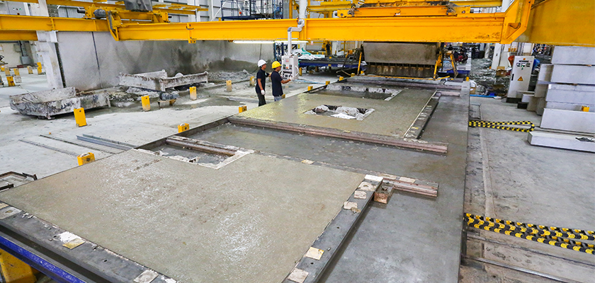 Two workmen supervise casting of panels in factory