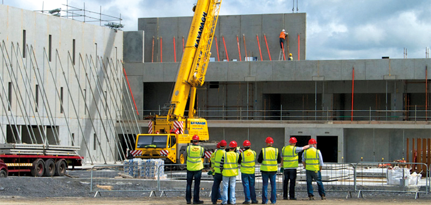 Onsite a team of workmen stand back in a row watching crane lift precast panel into position, prop's support panels